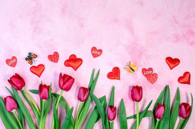 Tulipani rossi, cuori rossi e farfalle svolazzanti su uno sfondo rosa con texture con una copia dello spazio Foto Premium