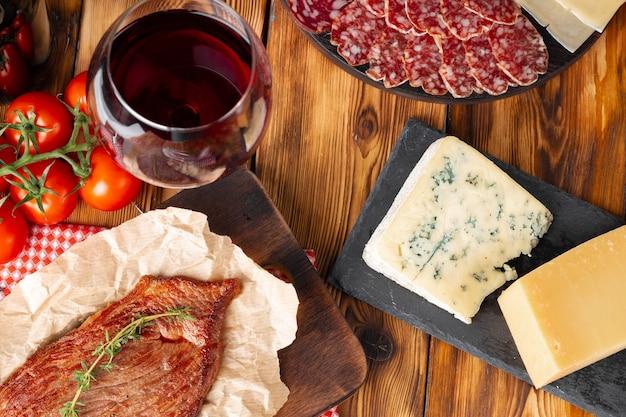 Vetro di vino rosso e blocchi di formaggio sulla tavola di legno si chiuda Foto Premium