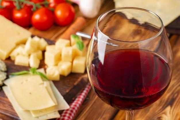Vetro di vino rosso e blocchi di formaggio sulla tavola di legno Foto Premium
