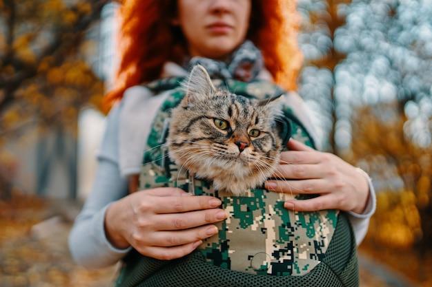 La donna dai capelli rossi sta camminando per strada portando un gatto in una borsa alla clinica veterinaria Foto Premium