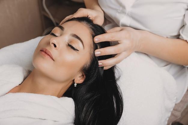 Bruna caucasica rilassata in attesa con gli occhi chiusi durante una procedura termale per pelle e capelli Foto Premium