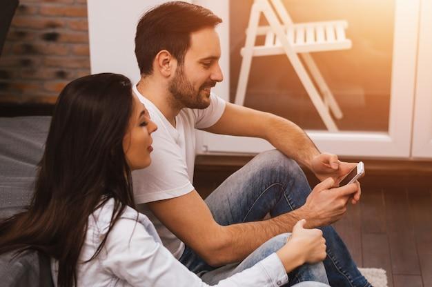 Coppie o amici rilassati che per mezzo di uno smartphone che si siede insieme sul pavimento nel salone a casa Foto Premium