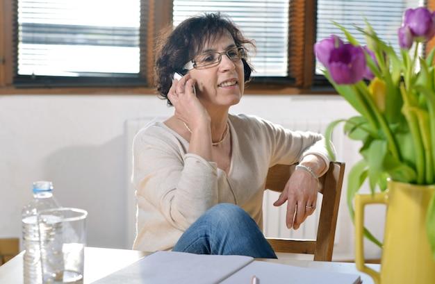 Donna castana matura rilassata in ufficio con uno smartphone Foto Premium