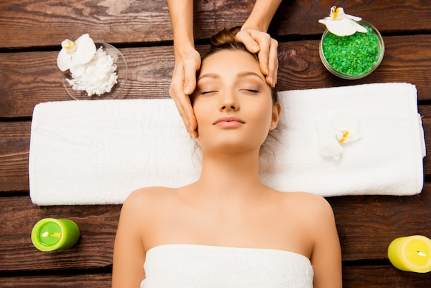 Giovane donna rilassata che risiede nel salone della stazione termale con gli occhi chiusi e avendo massaggio Foto Premium