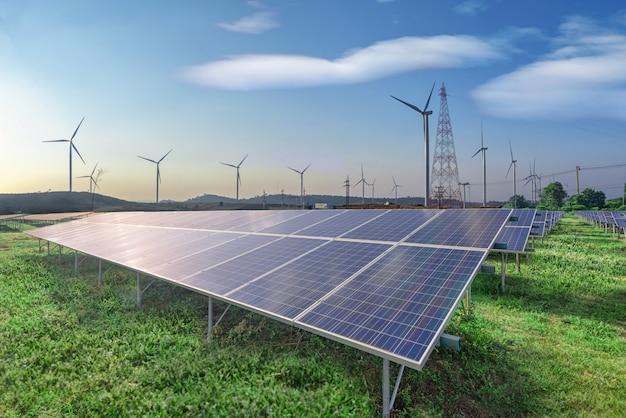 Energia rinnovabile, pannelli solari e turbine eoliche sull'erba verde nel cielo blu Foto Premium