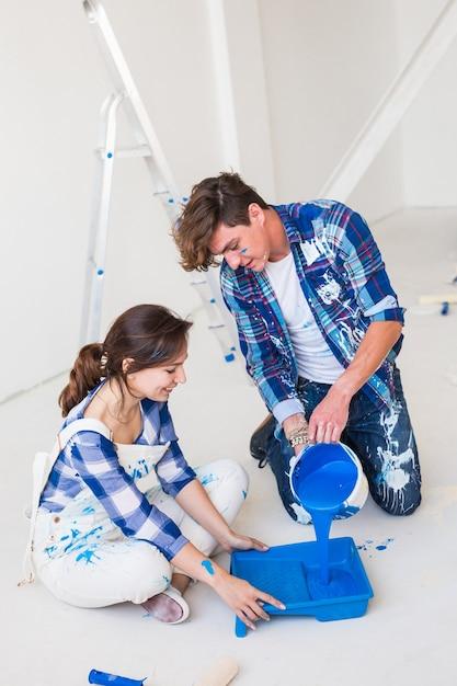 Riparazione, colore, concetto di persone - coppia che dipingerà il muro, stanno preparando il colore. Foto Premium