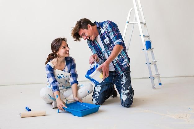 Concetto di riparazione, colore, ristrutturazione e persone: coppia che dipinge il muro, mescola il colore Foto Premium