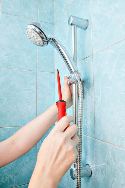 Sostituzione dell'impianto idraulico in bagno, doccetta a parete con staffa regolabile con regolazione ravvicinata e supporto per tubo flessibile. Foto Premium