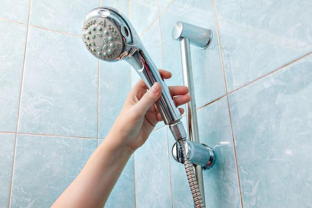 Sostituzione dell'impianto idraulico in bagno, doccetta a muro ravvicinata e supporto per tubo flessibile con guida scorrevole a barra regolabile in altezza. Foto Premium