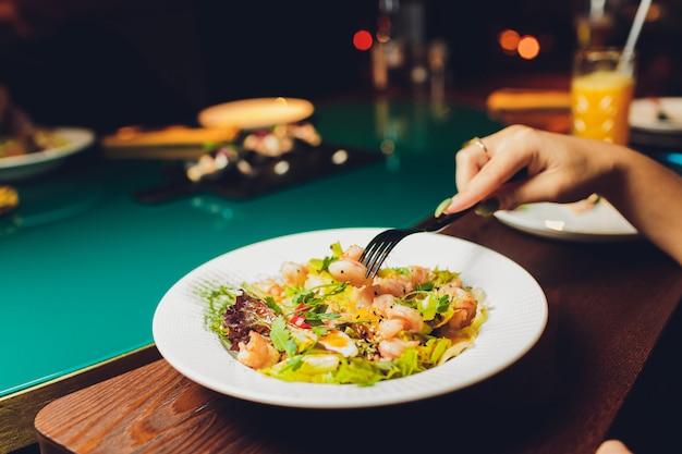 Tavolo ristorante o bar con piatto di insalate e vino. due persone che parlano sullo sfondo. immagine tonica. Foto Premium