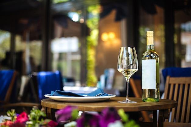 Tavolo in legno terrazza estiva ristorante servito con un piatto di vetro e una bottiglia di vino bianco Foto Premium