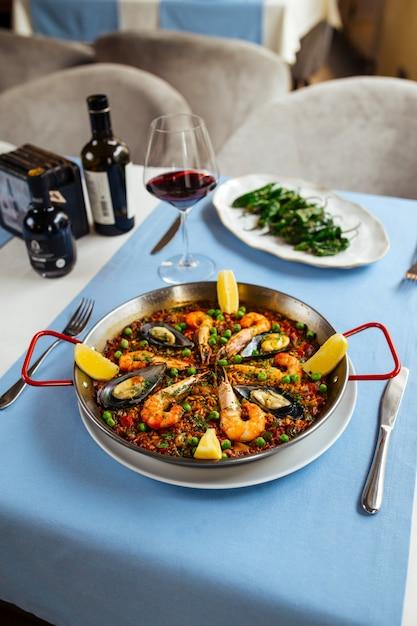 Tavolo del ristorante servito con piatti spagnoli, paella di pesce e peperoni padron Foto Premium