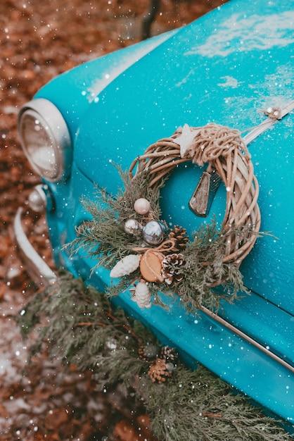Auto retrò decorata con rami di albero di natale festivi, scatole regalo con carta da regalo artigianale ghirlanda di aghi di pino e abete viaggio di capodanno. auto nella foresta di neve. Foto Premium
