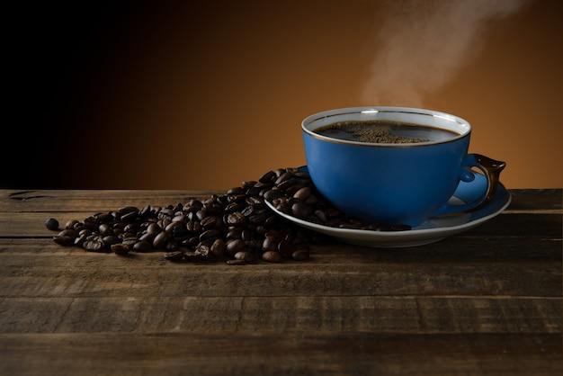 Retro tazza di caffè che esce di fumo sul tavolo rustico. Foto Premium