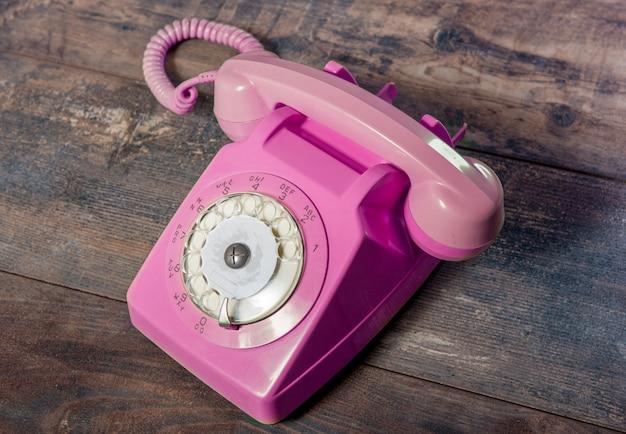 Retro telefono rotativo rosa sulla tavola di legno Foto Premium