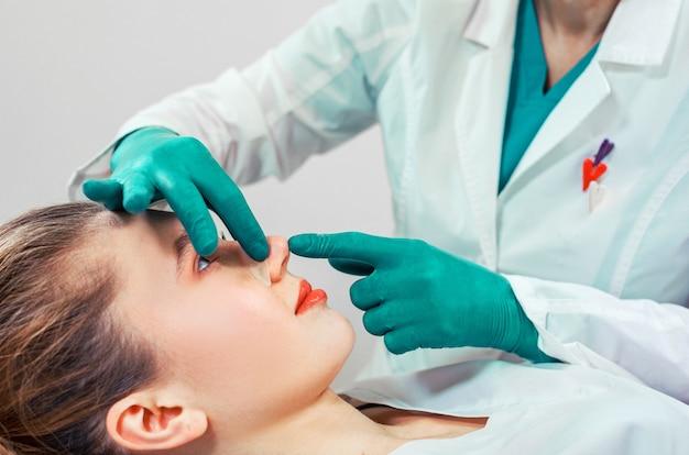 Rinoplastica, le mani del chirurgo toccano il naso del paziente. Foto Premium