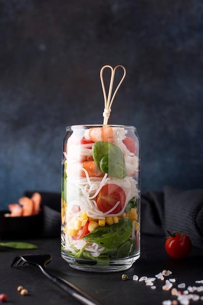 Spaghetti di riso con gamberetti e verdure in un barattolo di vetro su uno sfondo scuro, close-up Foto Premium