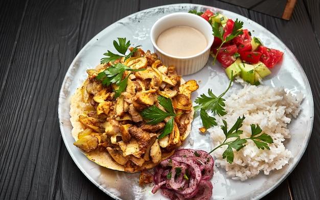 Riso con carne, funghi, verdure, pita e salsa, su uno sfondo nero Foto Premium