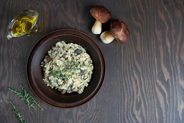Risotto con riso arborio, brodo, funghi e timo sulla tavola di legno marrone scuro Foto Premium