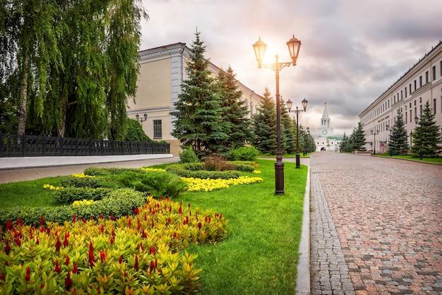 La strada dai blocchi di pietra alla torre spasskaya nel cremlino di kazan e bellissimi fiori Foto Premium