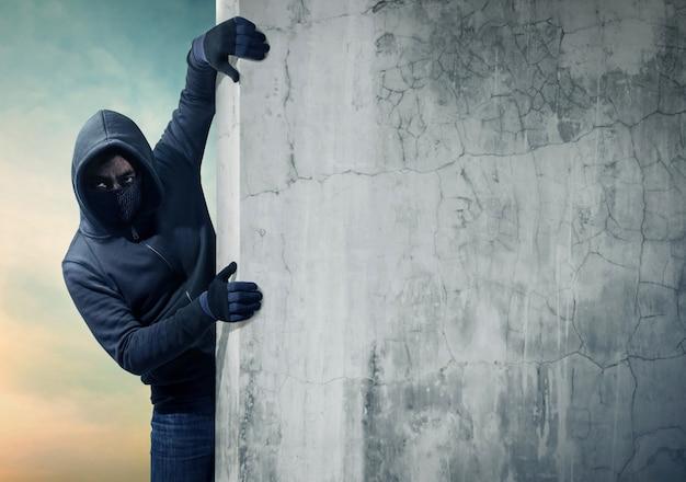 Ladro che si nasconde dietro un muro vuoto con spazio per il testo Foto Premium