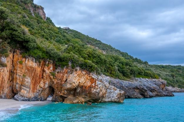 Riva della foresta rocciosa del mare in tempo nuvoloso. villa sul pendio. c'è un arco in pietra naturale sulla spiaggia Foto Premium