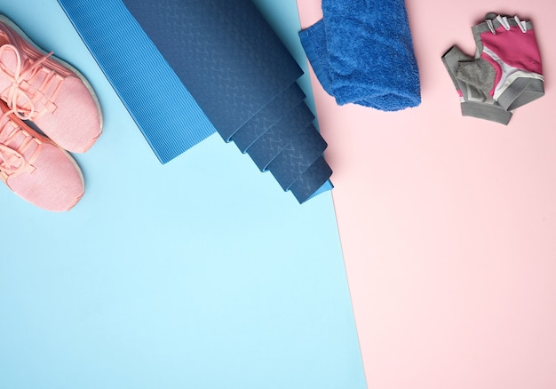 Tappetino sportivo arrotolato, scarpe da ginnastica rosa, asciugamano e guanti per lo sport Foto Premium
