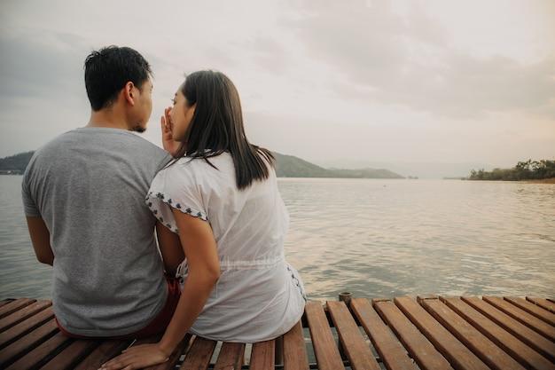 Coppie asiatiche romantiche che bisbigliano e godono della vista del lago. Foto Premium