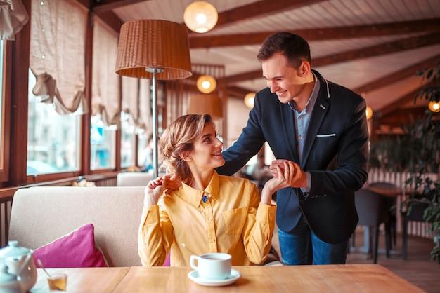 Appuntamento romantico delle coppie di amore nel ristorante. l'uomo in vestito abbraccia bella donna Foto Premium