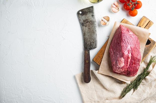 Set crudo di carne di manzo rotondo, sul tagliere di legno con il vecchio coltello da macellaio, vista dall'alto laici piatta Foto Premium