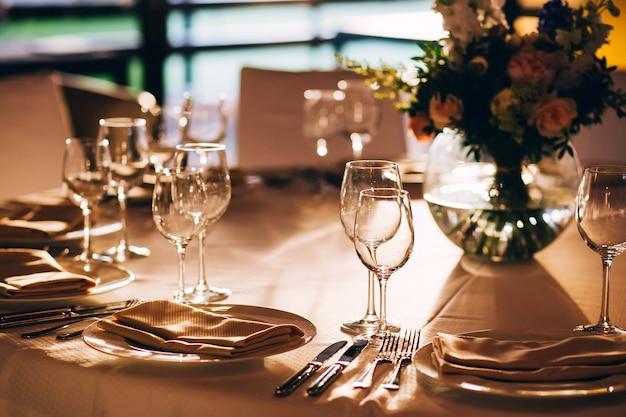 Tavolo rotondo con una tovaglia bianca. il tavolo è decorato con un vaso di fiori. bicchiere di vino e bicchiere di champagne. Foto Premium