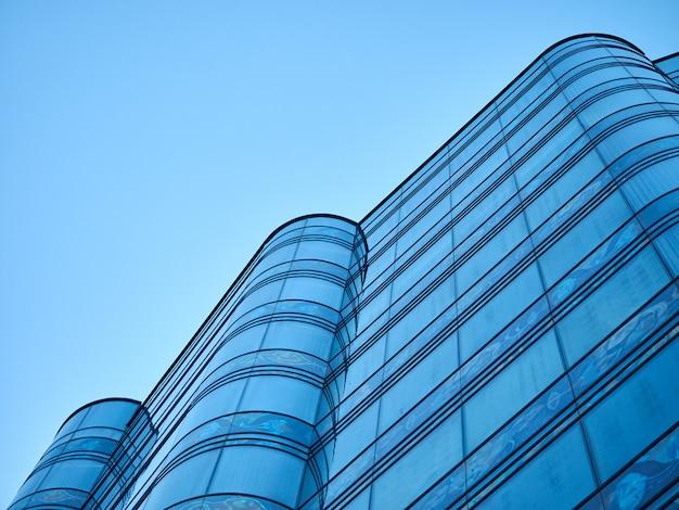 Edificio per uffici di vetro arrotondato su una priorità bassa della prospettiva del cielo blu Foto Premium