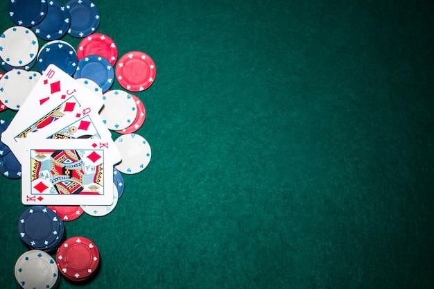 La carta da gioco del royal flush su fiches del casinò sopra la priorità bassa verde della mazza Foto Premium