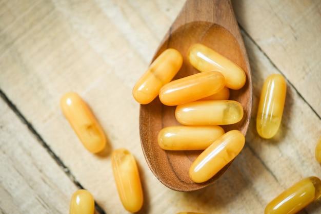 Capsule di pappa reale in cucchiaio di legno e tavolo in legno / capsula gialla medicina o cibo integrativo dalla natura per la salute Foto Premium