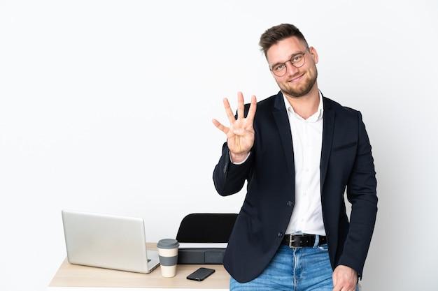 Uomo russo in un ufficio sul muro bianco felice e contando quattro con le dita Foto Premium