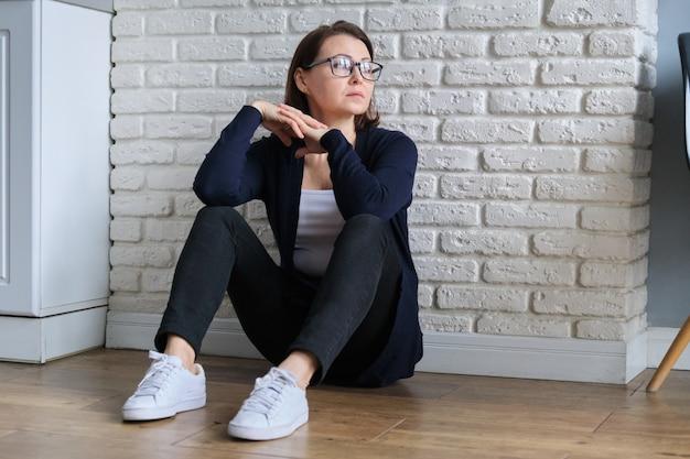 Donna sola triste di età depressa che si siede sul pavimento Foto Premium