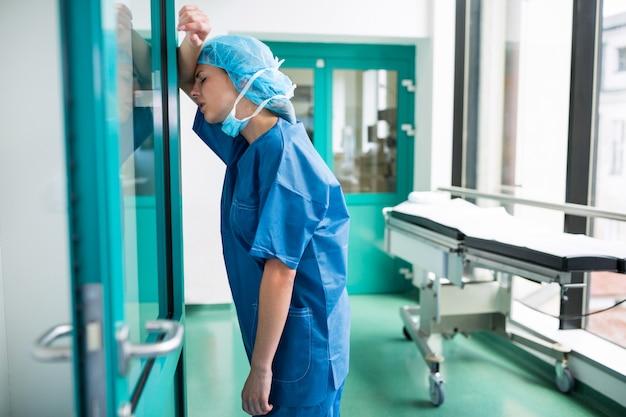 Triste chirurgo appoggiato alla porta a vetri Foto Premium