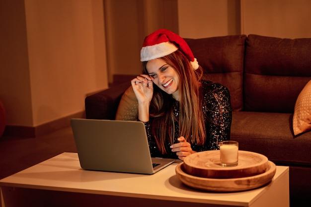 Giovane donna triste, vestita con un cappello di babbo natale che fa una videochiamata alla sua famiglia per festeggiare il natale. concetto di solitudine, famiglia separata, distanza sociale e natale. Foto Premium