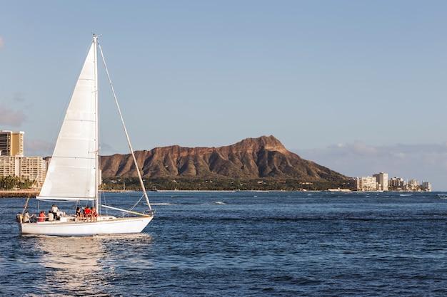 Barca a vela con sfondo di montagna diamond head, oahu honolulu hawaii Foto Premium
