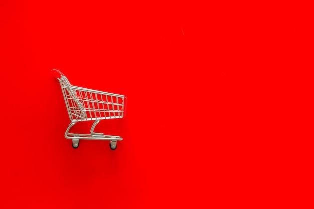 Concetto di vendita con carrello della spesa su sfondo rosso Foto Premium
