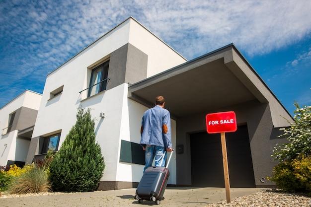 Per il concetto di immobile in vendita, uomo che esce di casa a causa della crisi economica Foto Premium