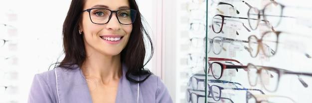 L'assistente alle vendite è in piedi accanto a una vetrina di ottica Foto Premium