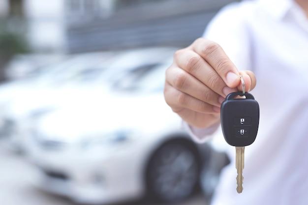 Venditore che tiene in mano una chiave dell'auto Foto Premium