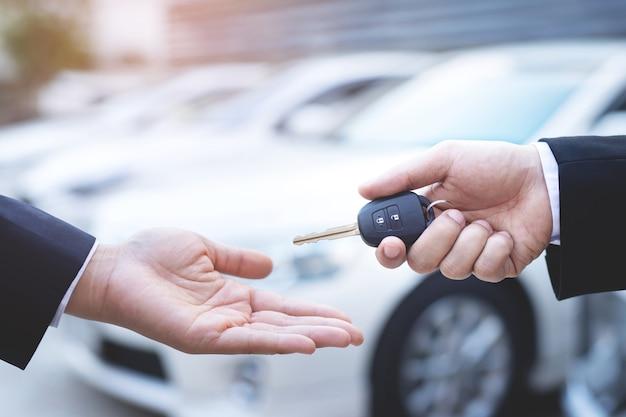 Il venditore consegna le chiavi della nuova macchina al cliente nello showroom. Foto Premium
