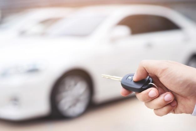 Il venditore apre e chiude la portiera dell'auto con la chiave. per sicurezza Foto Premium