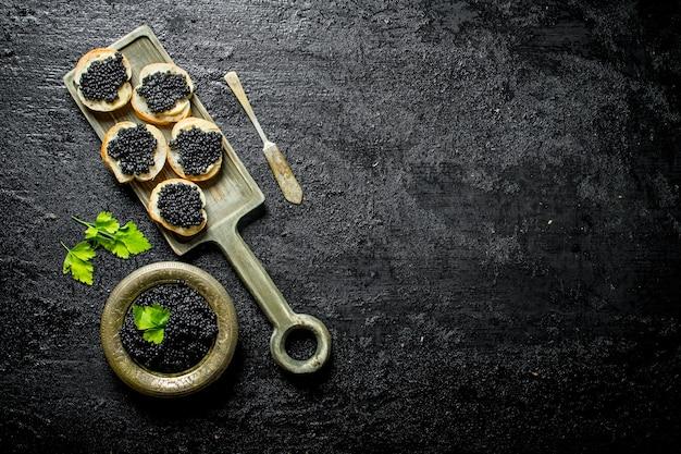 Panini con caviale nero sul tagliere. su sfondo nero rustico Foto Premium