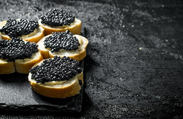 Panini con caviale nero su una tavola di pietra. sul nero rustico Foto Premium