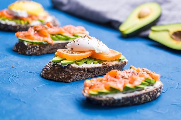 Panini con salmone affumicato, uova, salsa e avocado su sfondo blu. concetto di colazione e Foto Premium