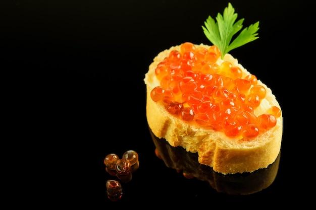 Sandwitch di fetta di pane bianco fresco con burro, caviale rosso e prezzemolo su sfondo nero riflettente. Foto Premium