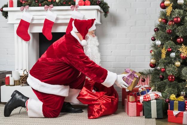 Santa mettendo regali sotto l'albero di natale Foto Premium
